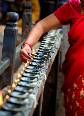 vrouw steekt wierook boter kaarsen, Nepal Stockfoto