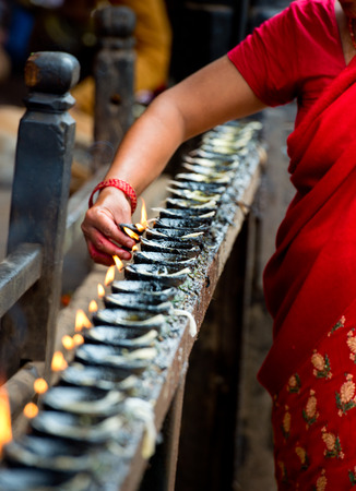 woman lights incense butter candles ,Nepal