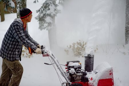 a blizzard: Winter blizzard: Clearing Snow with a Snow Blower Stock Photo