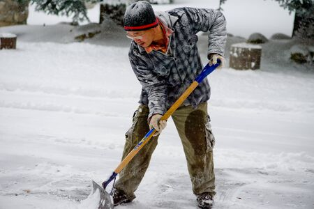 snow clearing: Winter blizzard: Clearing Snow with a Snow Blower Stock Photo