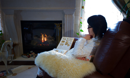 fireplace living room: Woman sitting in living room by fireplace Stock Photo