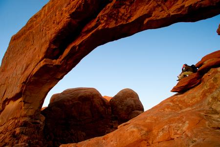 Man backpackers sitting on rocky ledge Stok Fotoğraf