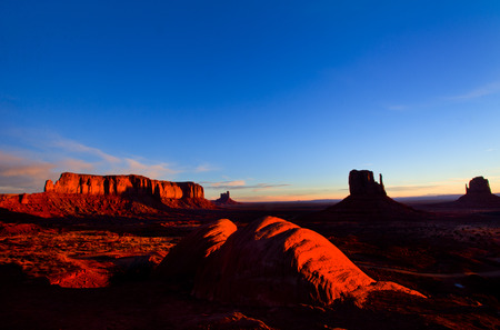 Monolith: The enthusiastic tourist in a white shirt in Monument Valley. The famous monolith of red sandstone - Mittens.