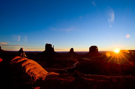 tribal park: The enthusiastic tourist in a white shirt in Monument Valley. The famous monolith of red sandstone - Mittens.