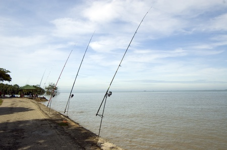 the row of  fishing rods and rails at the sea side
