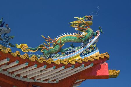 this is a asian chinese dragon statue at a chinese temple roof top with the clear blue sky as background Stock Photo - 9805724
