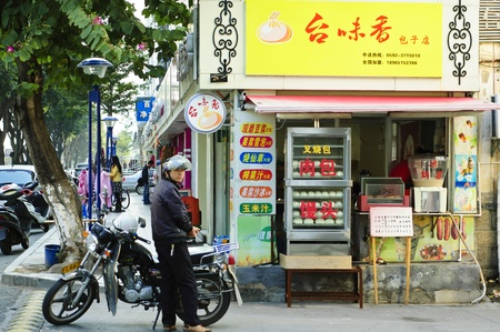 Xiamen, China , December 2, 2012 - A motorcycle rider waiting in front of a eatery shop