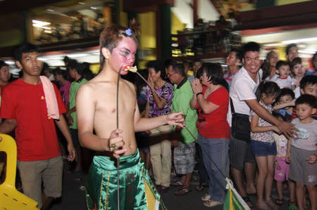 Johor, Malaysia - November 6, 2012 - the trance medium piercing himself during the Nine Emperor God Festival Celebration