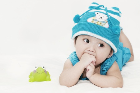 Little baby girl and a frog toy photo