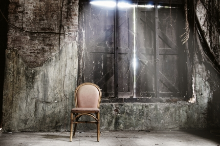 dirty room: Empty chair and ray of light