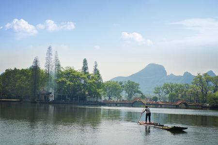 west bank: The old lady paddling her boat on the west bank of the Li Jiang River. Stock Photo