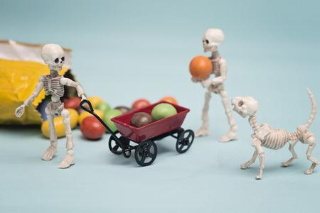 Dos niños esqueleto conseguir dulces de chocolate con el carro rojo Foto de archivo