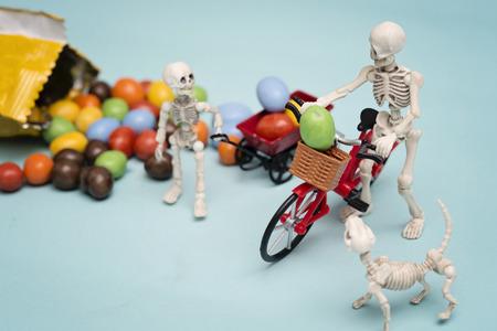 Esqueleto y su hijo esqueleto recibiendo caramelos de chocolate con la bicicleta
