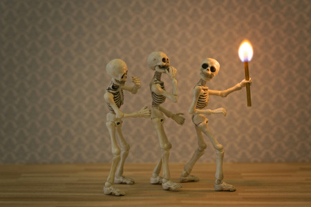 Three skeletons in the dark place with a torch