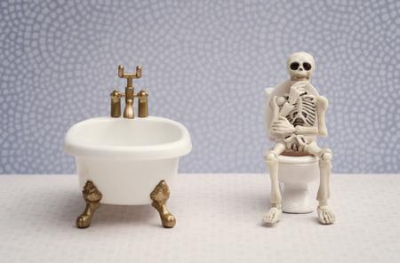 Skelett sitzt auf Wasserklosett beim Denken Standard-Bild - 60902288