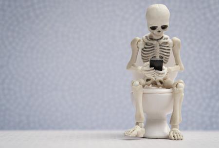 Skeleton immer mit seinem Smartphone beschäftigt, während auf dem Wasser Schrank sitzt Standard-Bild - 60902300