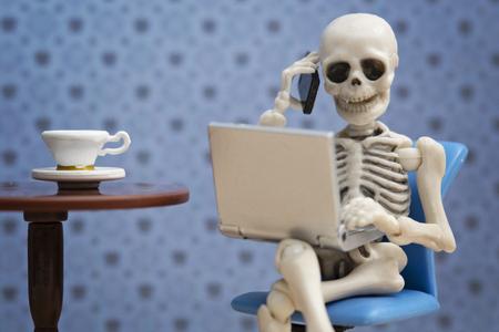 Skelett ruft mit Laptop auf seinem Schoß Standard-Bild - 60902314