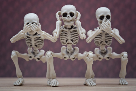 Three skeletons pose as three wise monkey Stock Photo