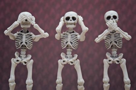 Three skeletons pose as three wise monkey Stock Photo