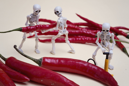 aliments droles: Three skeletons pumping red chili pepper