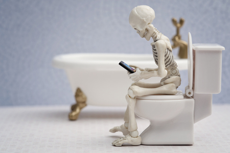water closet: Skeleton getting busy with his smartphone while sitting on water closet