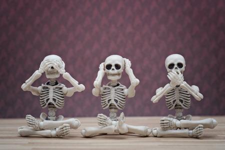see: Three skeletons pose as three wise monkey Stock Photo