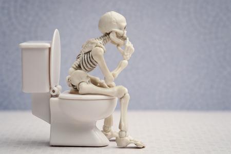 Skelett sitzt auf Wasserklosett beim Denken Standard-Bild - 63958900