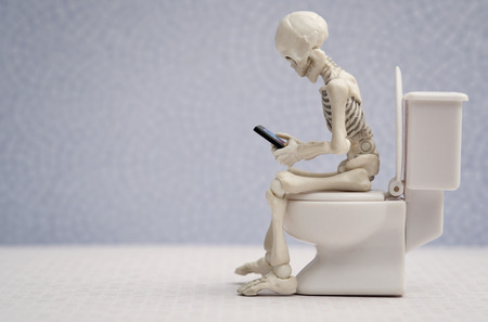 Esqueleto sentado en inodoro un teléfono inteligente en la mano