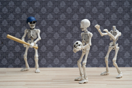 Two skeletons use their friends head playing baseball