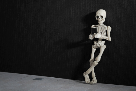 Een skelet leunend op een grungy muur met smartphone in zijn hand