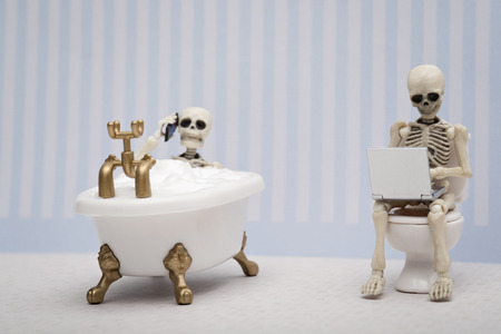 A skeleton talking on the phone while having bubble bath and other skeleton sitting on water closet with laptop on his lap Stock Photo