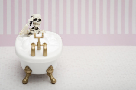 A skeleton talking on his cellphone while having bubble bath
