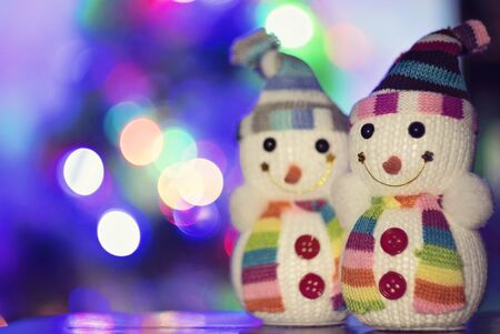 Toy snowman and Christmas lights in the background Stock Photo