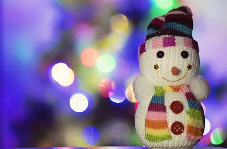 Toy Schneemann und Weihnachtsbeleuchtung im Hintergrund Standard-Bild - 88972597