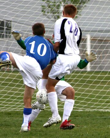 Soccer players attacking and defending the goal.