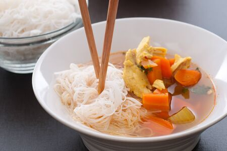 Chicken broth soup with carrot, onion, celery and chicken  Served with rice noodles  photo