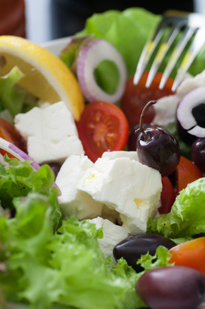 spanish onion: Green salad feta cheese, black olives, tomatoes, spanish onion. Served with olive oil, pepper and lemon. Stock Photo