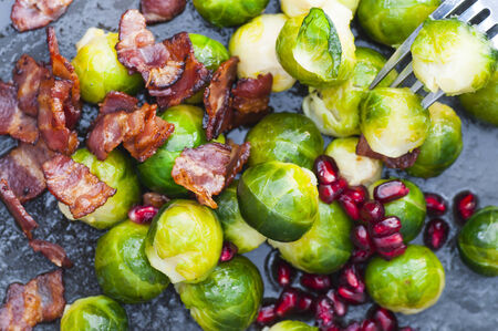 buttered: Buttered brussels sprouts with bacon and pomegranate. Stock Photo