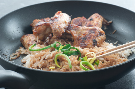 leftovers: Leftovers. Fried rice with with soy sauce, barbecue chicken wings and leek in a frying pan. Stock Photo