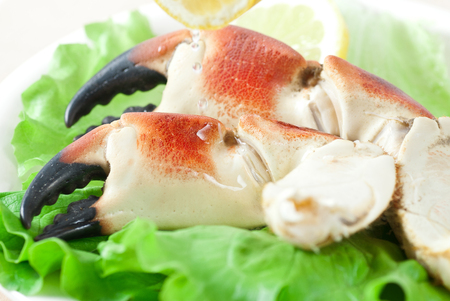 Prepared crab claws with green lettuce and lemon.