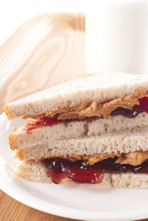 jelly sandwich: Peanut butter and jelly sandwich with a glass of milk.