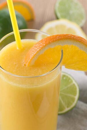 jus orange glazen: A glass orange juice with straw and a slice orange.