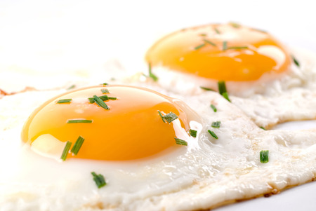 chive: Two fried eggs with chive on top.