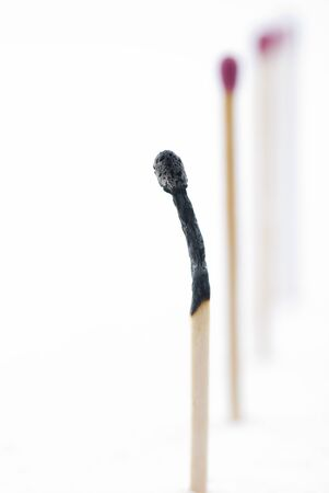 burned out: Matches in a row describing burnt out caused by stress.Focus on top of burned match. Stock Photo
