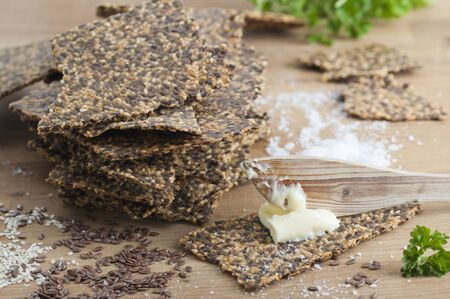 organic flax seed: Homemade gluten free flax seed and sesame seed crispbread with butter and sea salt. All organic. Stock Photo