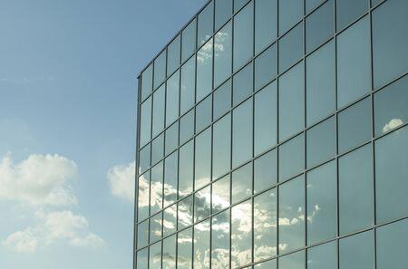 青空に白い雲と輝く太陽を持つオフィスビルの窓