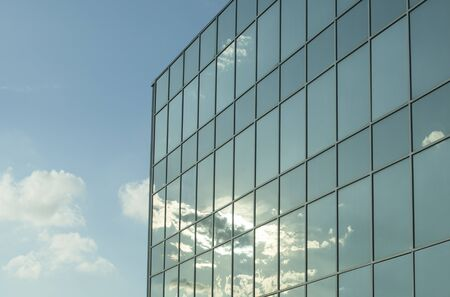 Office building windows with white clouds and shining sun in a blue sky