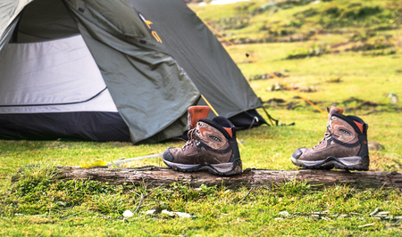camping tent: Tracking shoes in front of the tent on the green grass background Stock Photo