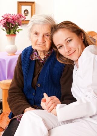 Jonge arts houdt van de oude vrouw handen Stockfoto