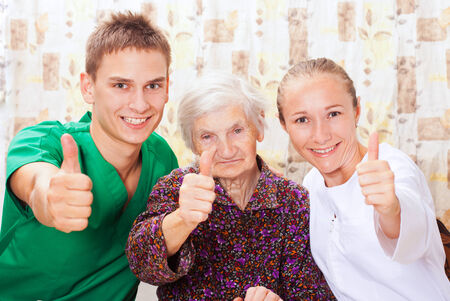 nursing aid: Elderly woman with the sweet young doctors Stock Photo